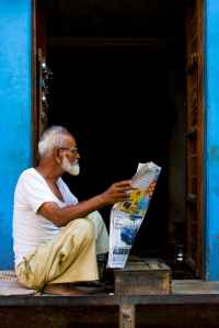 old man sitting while holding newspaper article